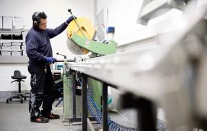 Mitarbeiter schneidet eine Schiene mithilfe einer Kappsäge zurecht