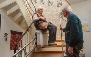 Ältere Dame fährt Treppenlift auf kurviger Treppe probe