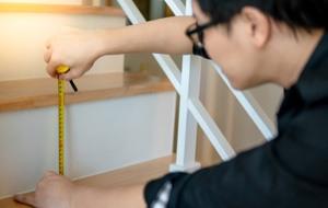 Der Treppenlift Mitarbeiter vermisst eine Treppe Der Treppenlift berät sie zu den Möglichkeiten einer Treppenliftmiete
