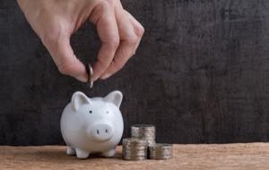 Person wirft Münzen in ein Sparschwein