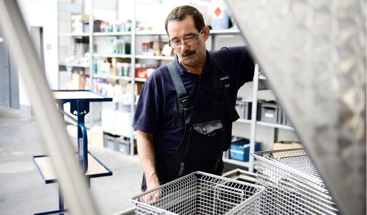Mitarbeiter reinigt mithilfe eines Industriereinigers verschmutzte Lift-Teile
