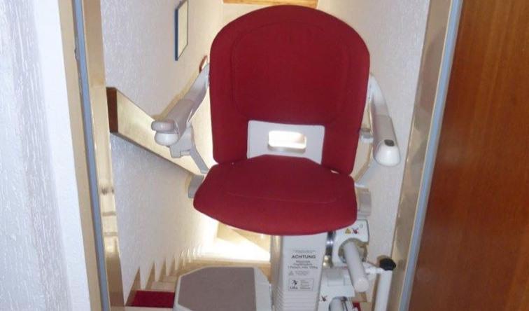 Einbaubeispiel eines gebrauchten Sitzliftes mit rotem Polster von Der Treppenlift