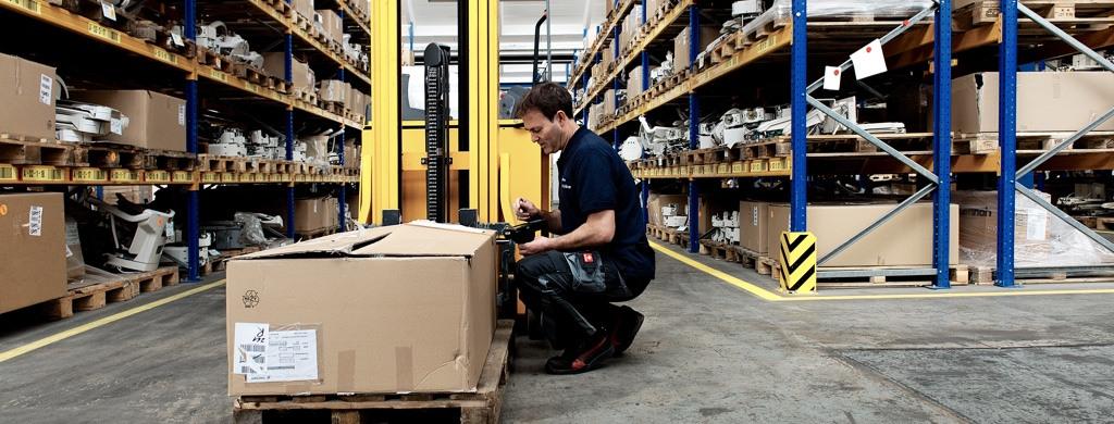 Der Treppenlift-Mitarbeiter packt in einer Lieferhalle einen gerbauchten Lift aus