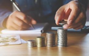 Mann zählt am Schreibtisch Kleingeld und stapelt es