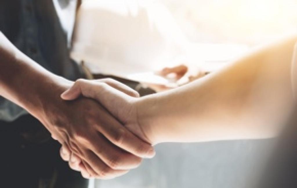 Zwei Personen schütteln sich die Hand