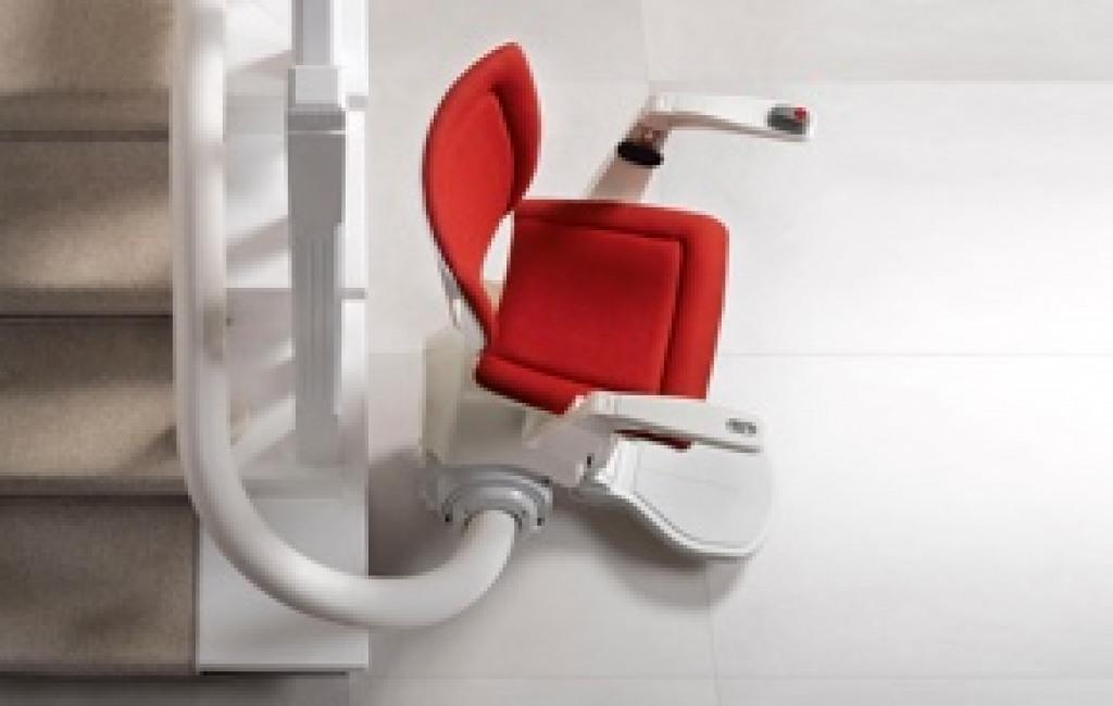 Gebrauchter Sitzlift im Treppenhaus mit rotem Polster